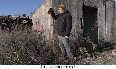 Drunk man with empty wine bottle near abandoned building
