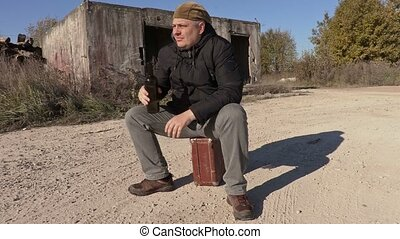 Drunk man with empty wine bottle sitting on the suitcase