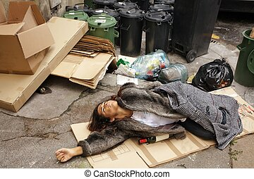 drunk tramp woman lying on cardboard in city trash area