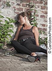 Drunk woman at the brick wall