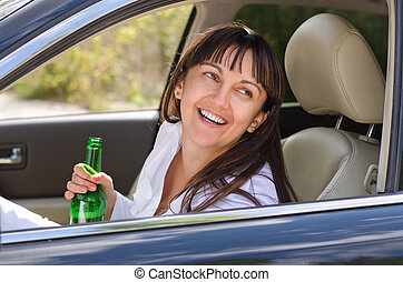 Drunk woman driving laughing out of the side window as she...