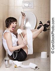 Drunk woman sitting dizzy on the toilet floor