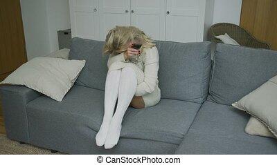 Drunk woman with wine sitting on sofa - Sensual drunk woman...