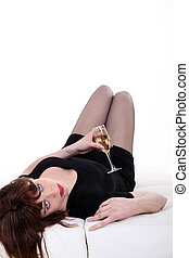 drunk young woman lying in sofa with flute of champagne
