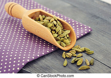 Dry cardamom seeds in scoop closeup on wooden background