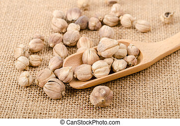 Dry cardamom seeds in wooden scoop.