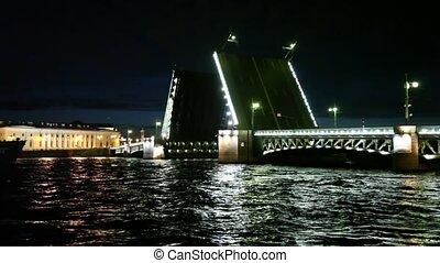 Dry cargo ship floats through raised bridge night on Neva river