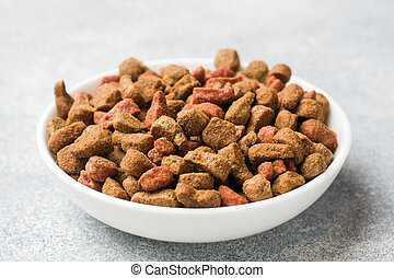 Dry cat food in a ceramic plate.