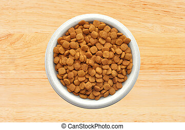 Dry cat food in plate over wooden background