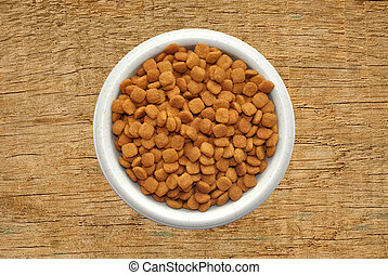 Dry cat food in plate over wooden texture