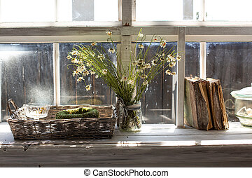 Dry chamomile flowers in a vase on a windowsill with a books