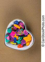 Dry colorful play dough in heart shaped bowl