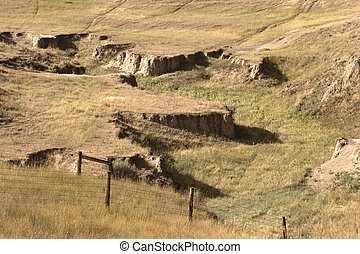 Dry Creekbed Ravine and barbed wire fence in rural...