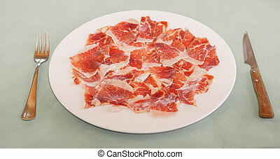 dry-cured ham slices on plate in restaurant
