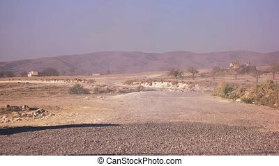 Dry dusty road with mountains on the background.