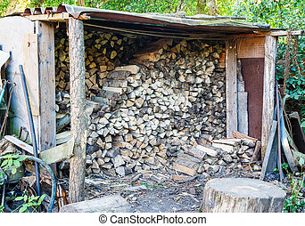 firewood stacked in a woodpile - dry firewood stacked in a...