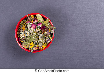 Dry flower and herbs tea background in red bowl, top view, close up, copy space
