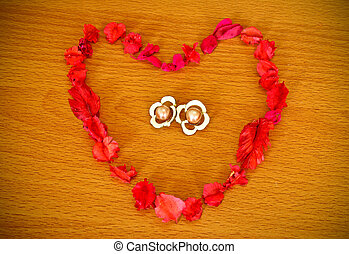 Dry flower heart with earrings on wood background
