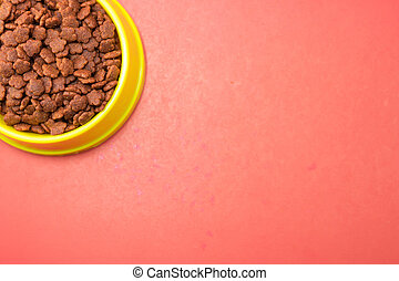 Dry food in bowls for pet on red background.