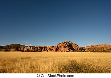 Dry Grassy Field And Red Rocks At Sunset