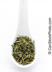 Dry green tea leaves in a spoon