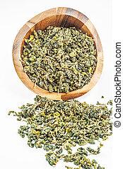 Dry green tea leaves in wood cup is