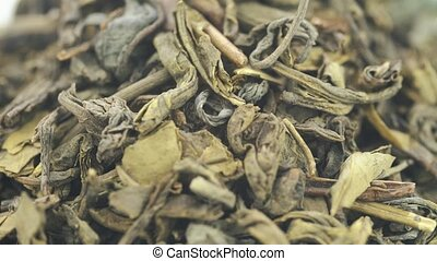 Dry green tea lies on the table. The frame rotates clockwise.
