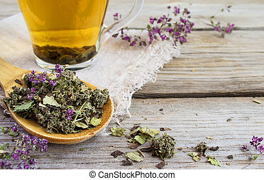 Dry herb tea on a background of cups with tea