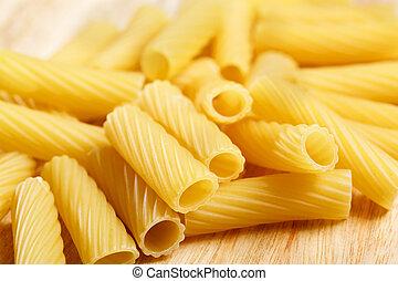 Dry italian pasta penne on wooden board