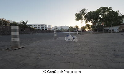 Plastic bag traveling around the city with dry leaves being blown by the wind. Empty city street at sunset