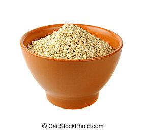 dry oat grains in brown clay bowl