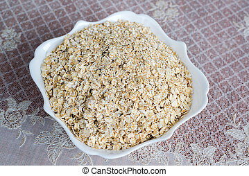Dry oatmeal in a plate on table