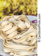 Dry uncooked pappardelle pasta nests in food ingredient image