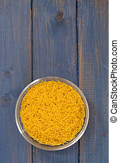 dry pasta in bowl on blue background