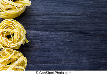 Dry pasta - Organic fettuccine nests pasta on wood board.