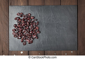 Dry red cranberries on a slate plate with copy space