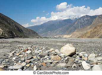 A dry stoney river bed amid the mountains and hills of Nepal.