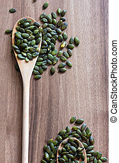 Dry roasted pumpkin seeds on in wooden spoon on wooden tabletop