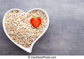 Dry rolled oatmeal in bowl. - Fried oat flakes in a heart...