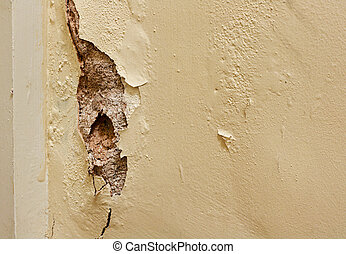 Damaged plaster wall in need of renovation by painters and decorators inside a residential home