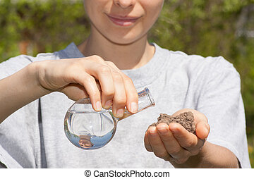 dry soil in hand and a flask with water
