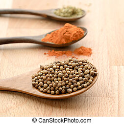 Dry spices in spoons and green herbs on the wooden table (close up)
