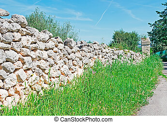 dry stone wall and grass on a sunny day