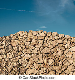 Arched dry stone wall with a blue sky on background