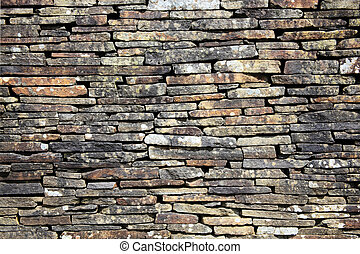 Dry stone wall stacked high to form a boundary