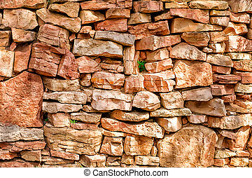 Decorative dry stone wall with small herb at sunlight