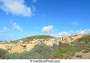 dry stone wall under a cloudy sky in Sardinia