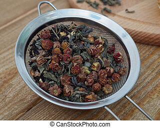Dry strawberries in a sieve on a wooden background close-up. Aromatic herbal tea with berries. Healthy delicious tea made from berries and herbs