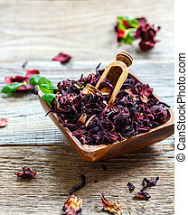 Dry tea Hibiscus in a square wooden bowl.
