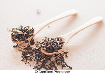 Dry tea in wooden spoons